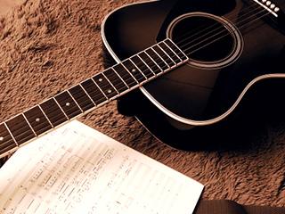 床に置かれたギターと楽譜
