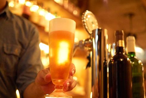 バーカウンターからコップに注いだビールを提供しようとしている